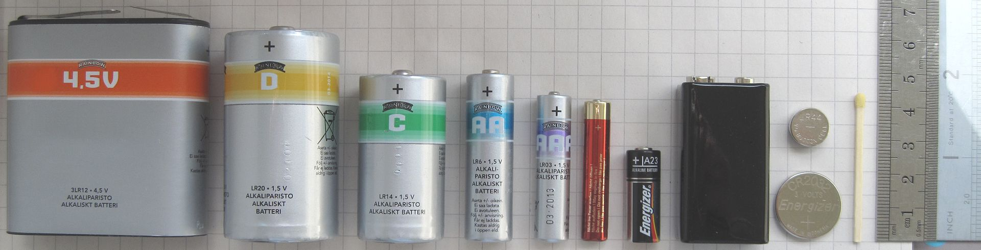"Common Alakali batteries, from left to right: 4.5v (""Lantern battery""), D, C, AA, AAA, AAAA, A23, 9V, CR2032, LR44, and finally a matchstick and ruler for comparison."